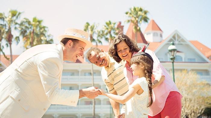 Un guide VIP costumé accueille un jeune visiteur et sa famille devant leur hôtel