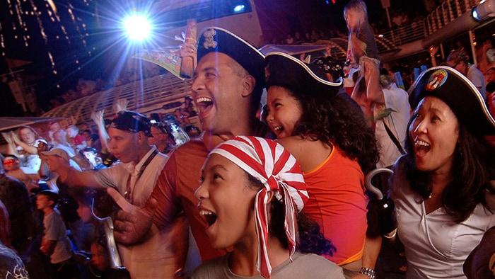 Fantasiados de pirata, os integrantes de uma família admiram os fogos de artifício em uma festa no deck a bordo da Disney Cruise Line