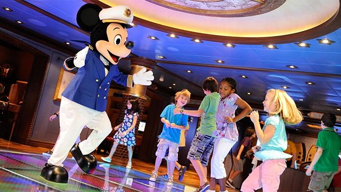 Fantasiado de capitýo de navio, Mickey Mouse danýa com výrias crianýas.