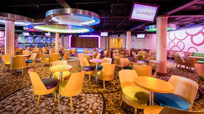 Um lounge supercolorido com grandes lustres redondos, decoração com círculos e um palco.