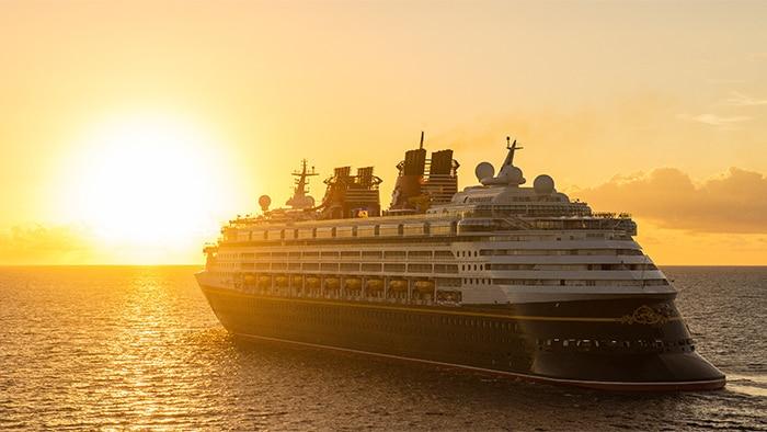 O Disney Magic, um navio com vários decks, em alto-mar com um brilhante pôr do sol ao fundo.