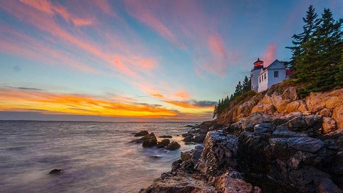 Un coucher de soleil colore les nuages au-dessus d'une falaise rocheuse et d'un phare