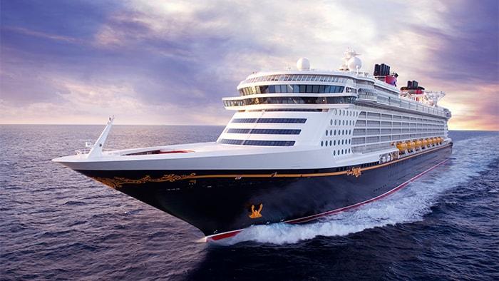 El crucero Disney Dream, un barco de mýltiples pisos, en mar abierto, dejando una estela de espuma