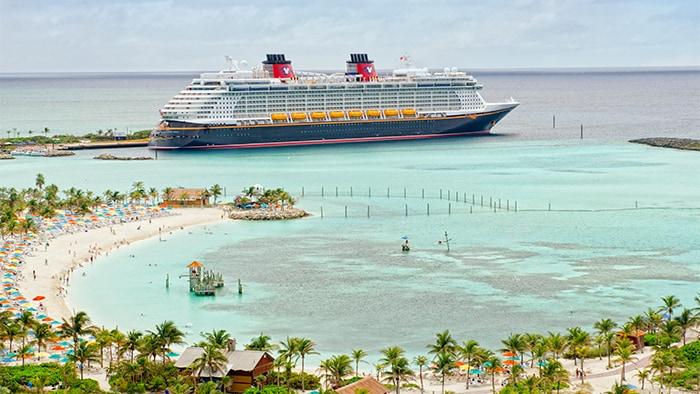Pessoas, guarda-sóis e palmeiras delineiam a curva da baía da Castaway Cay, com o Disney Fantasy atracado ao fundo.