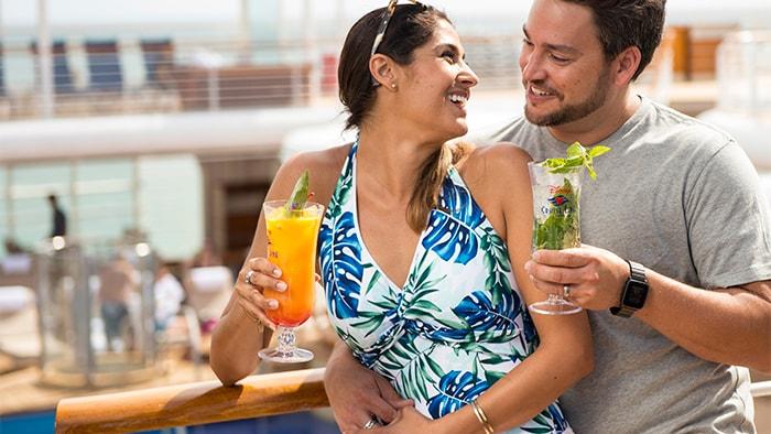 Um homem e uma mulher sentados bem próximos de mãos dadas em um bar externo do navio, segurando bebidas em taças altas.