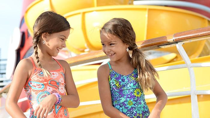 Duas garotas se divertem em frente ao toboágua de um navio da Disney Cruise Line.