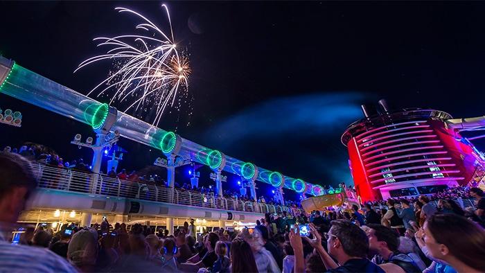 Uma multidão tira fotos dos fogos de artifício estourando acima das luzes neon do deck, à noite.