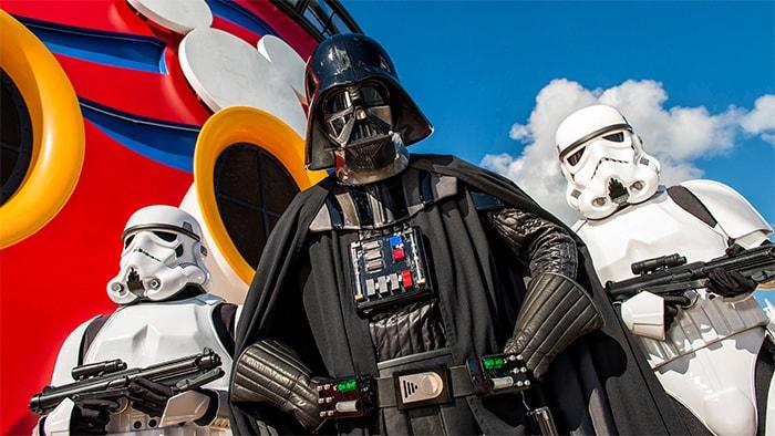 Darth Vader, escoltado por dois stormtroopers, faz uma pose ameaçadora com o logotipo da Disney Cruise Line atrás.