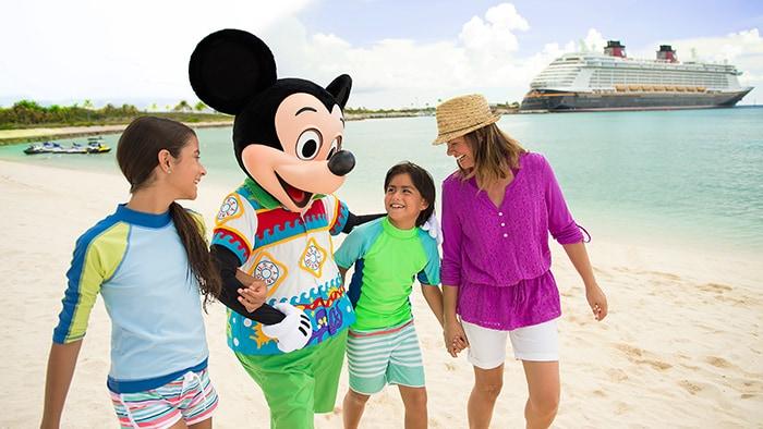 Una mamá y sus 2 niños caminan de la mano con Mickey Mouse en la playa