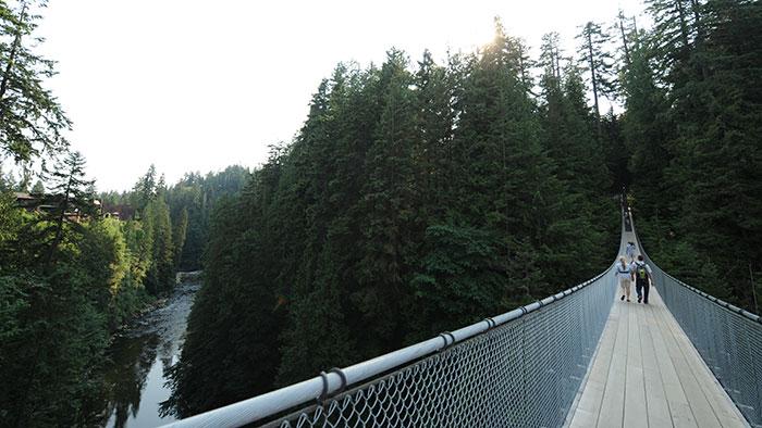 Des gens marchent sur un pont au-dessus d'une rivière dans une forêt