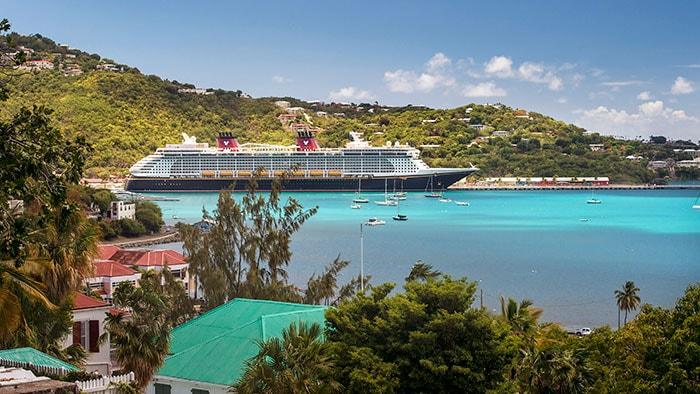 Un navire de croisière Disney près d'une île avec des bâtiments et des arbres