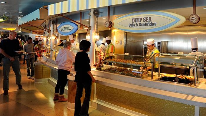 Des gens dans une aire de restauration où une affiche indique «Deep Sea Subs and Sandwiches»
