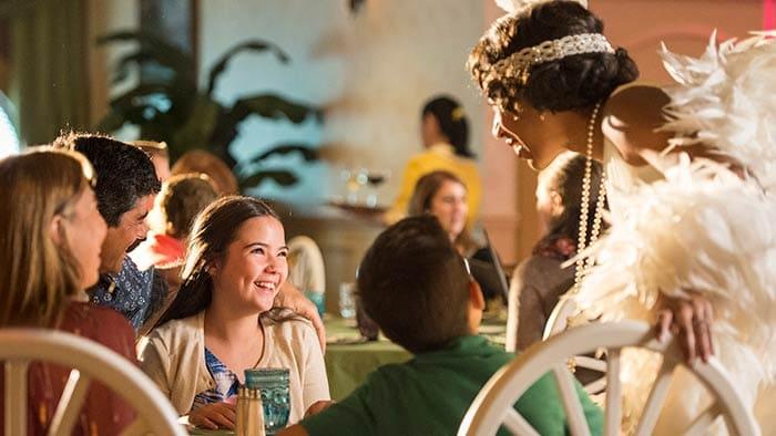 Une famille rit avec Tiana dans un restaurant