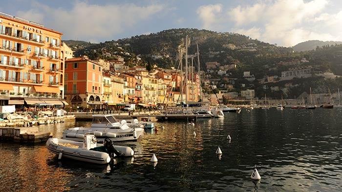 Des bateaux dans une marina près d'une ville et d'une montagne