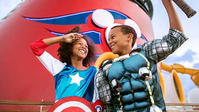Une fille costumée comme Captain America pose à côté d'un garçon costumé comme Thor