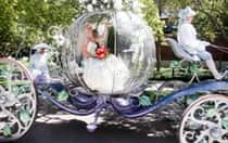 A bride holding a bridal bouquet and sitting inside Cinderella's Coach