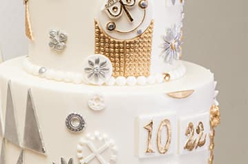 A wedding cake adorned with charms and silver flowers