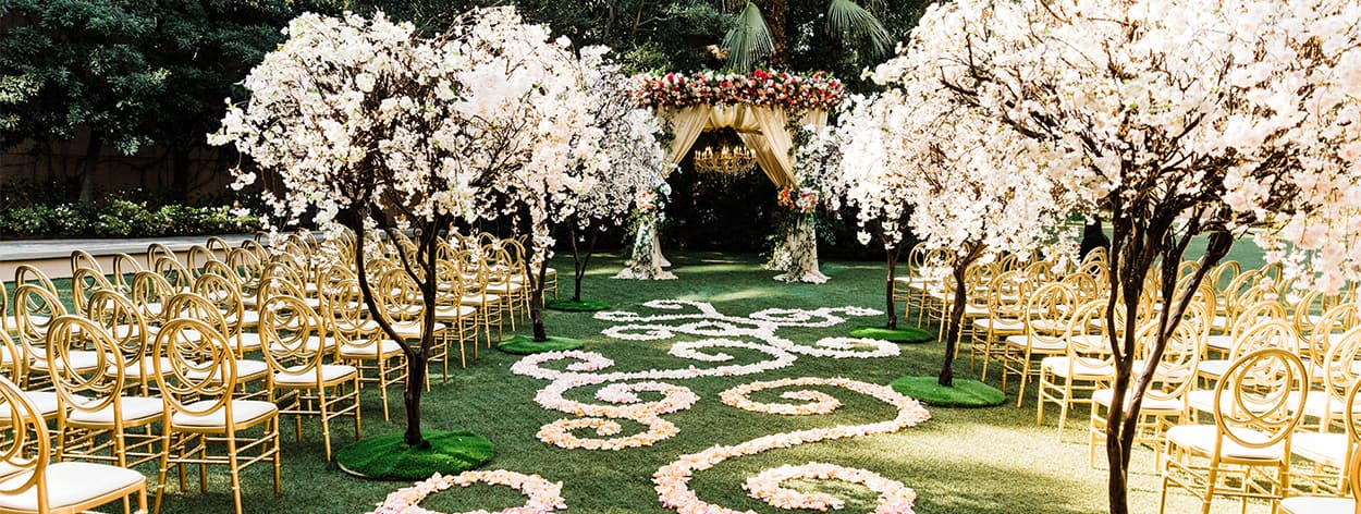 A lawn arranged for a wedding ceremony featuring a flower adorned altar, a wide aisle and many rows of chairs