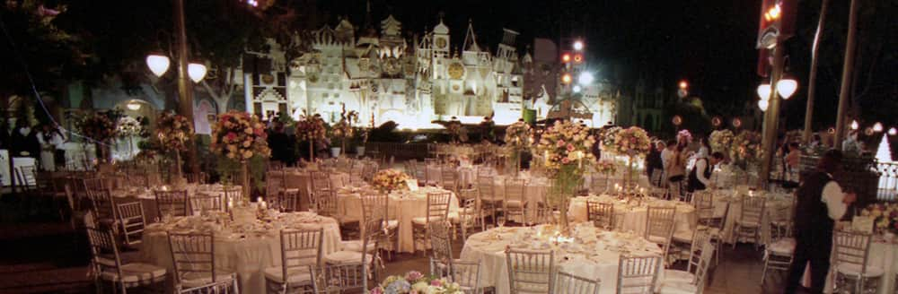 A large wedding reception outside of 'it's a small world'