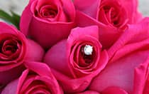 A diamond shaped charm in the middle of a rose bouquet