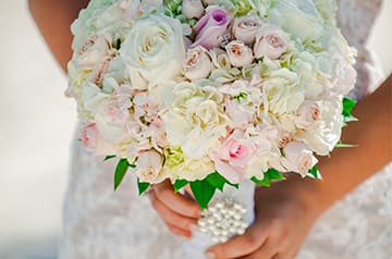 A bride holding a bouquet of flowers adorned with pearls