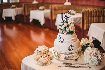 A small wedding cake on a table with 3 floral bouquets