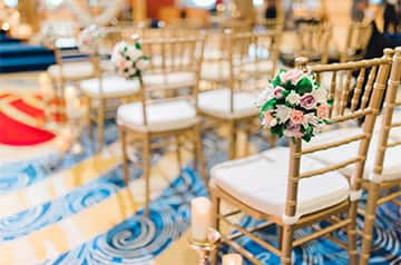 Floral arrangements tied to the sides of chairs arranged in rows