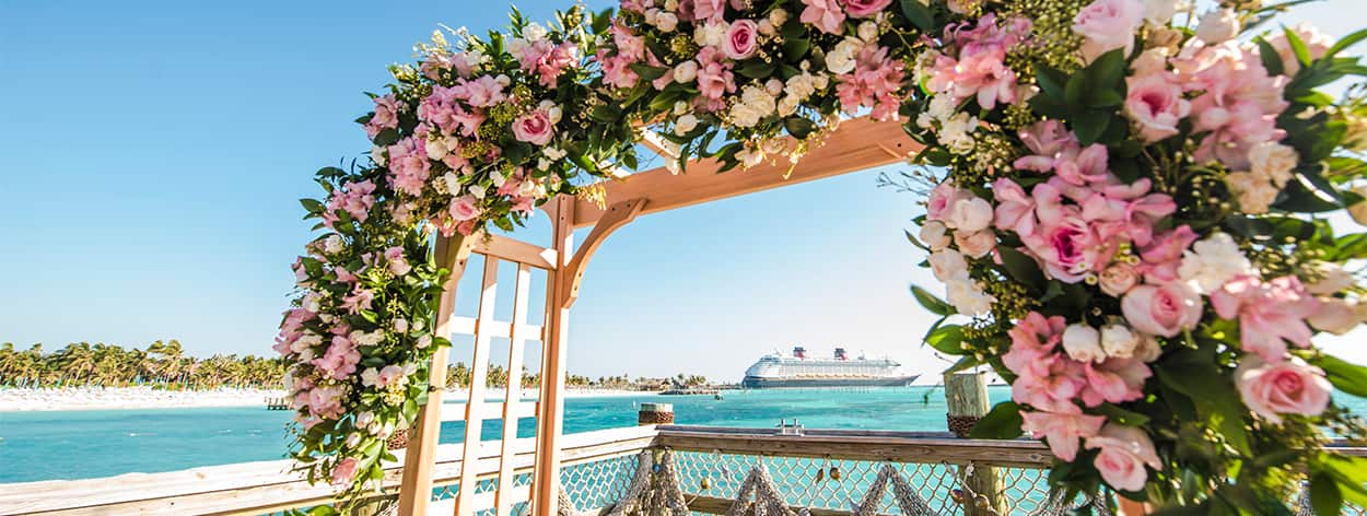 A Disney Cruise Line Ship positioned near an archway covered with flowers
