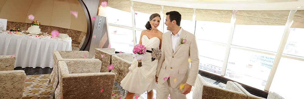 Flower petals fall through the air while a bride and groom walk through their reception hall