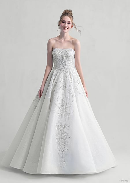 A woman stares down at the Cinderella wedding gown from the 2021 Disney Fairy Tale Weddings Platinum Collection that she is wearing
