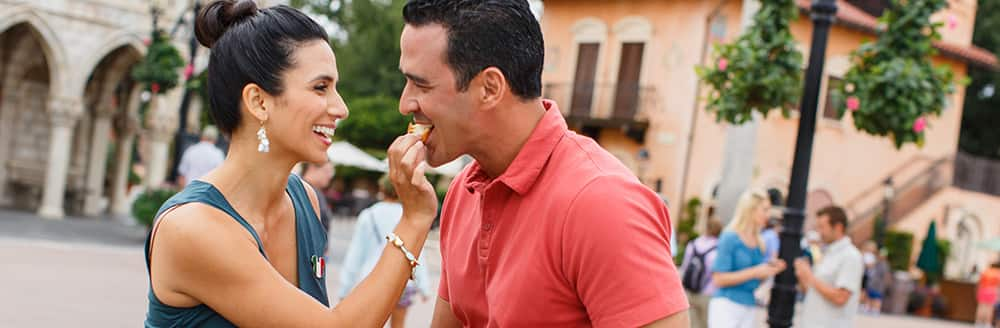 A man and woman share a snack in the Italy Pavilion at Epcot in Florida