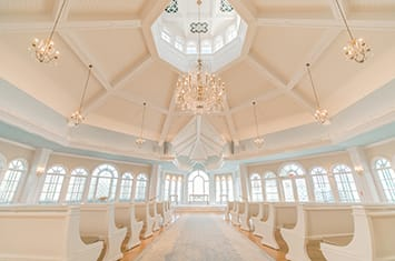 The Disney Wedding Pavilion at Walt Disney World Resort with 2 rows of pews with an aisle leading towards an altar beneath a round ceiling with hanging lights