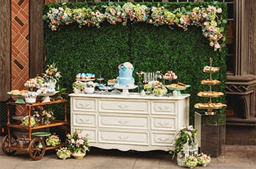 A wedding cake and an assortment of desserts on a dresser set under an arrangement of flowers