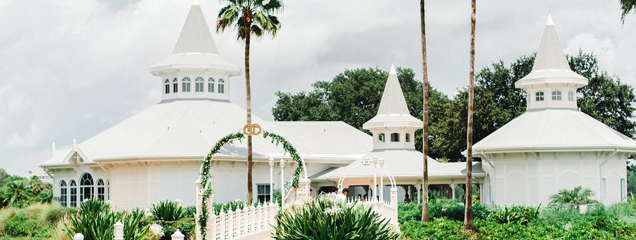 Lush trees and bushes surround a bridge leading towards the Wedding Pavilion