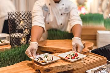 A Disney chef places 2 plates of appetizers on a table