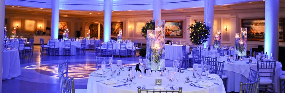Tall glass centerpieces on round tables in the rotunda at the American Adventure attraction