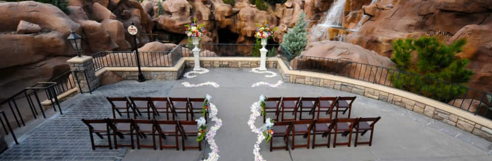 Two sections of folding chairs facing an altar in front of a waterfall