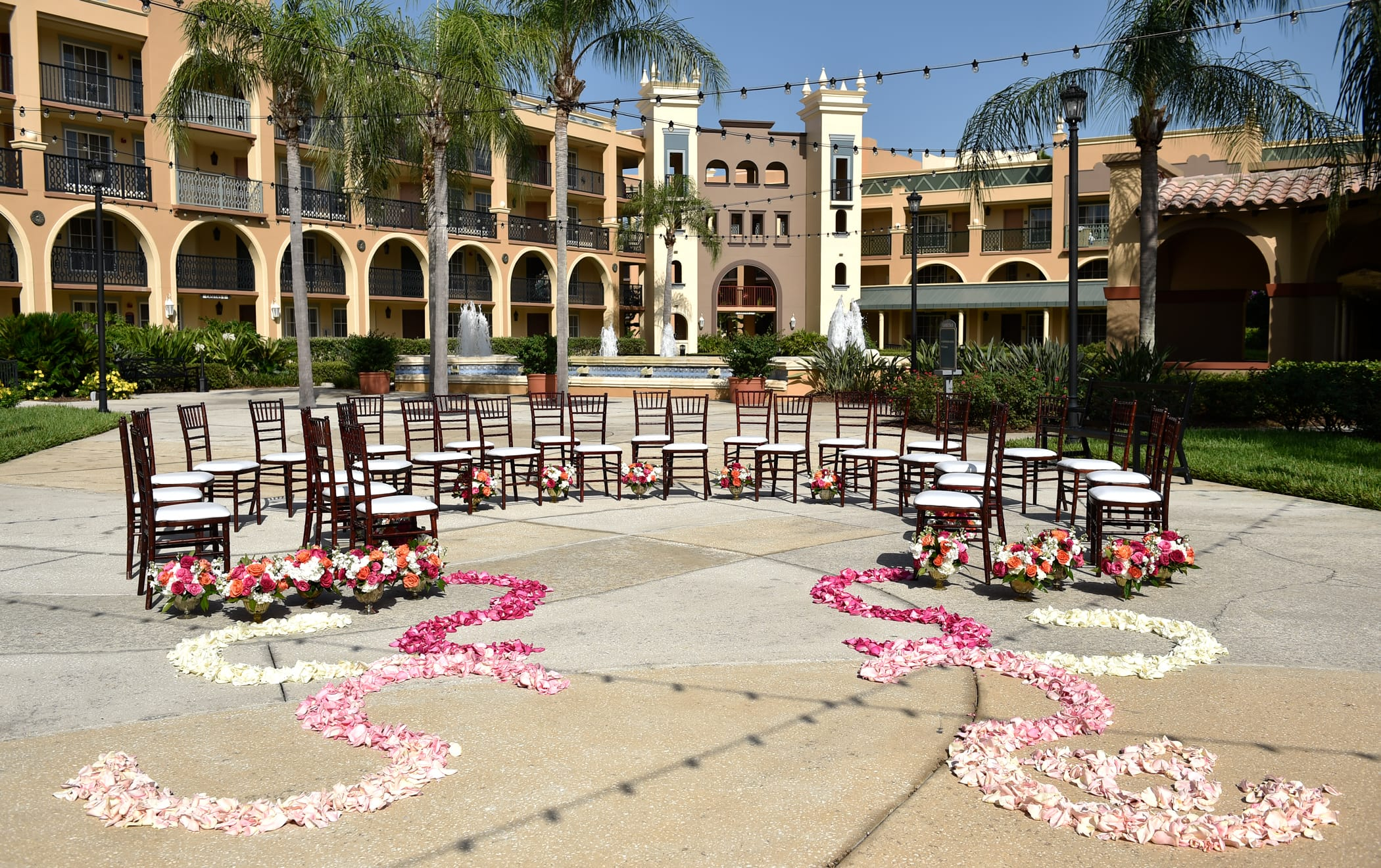 Rose petals lead to a group of chairs arranged in a semi-circle on a courtyard with a large water fountain