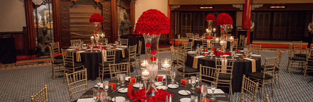 Round tables with place settings and large bouquets of roses as centerpieces