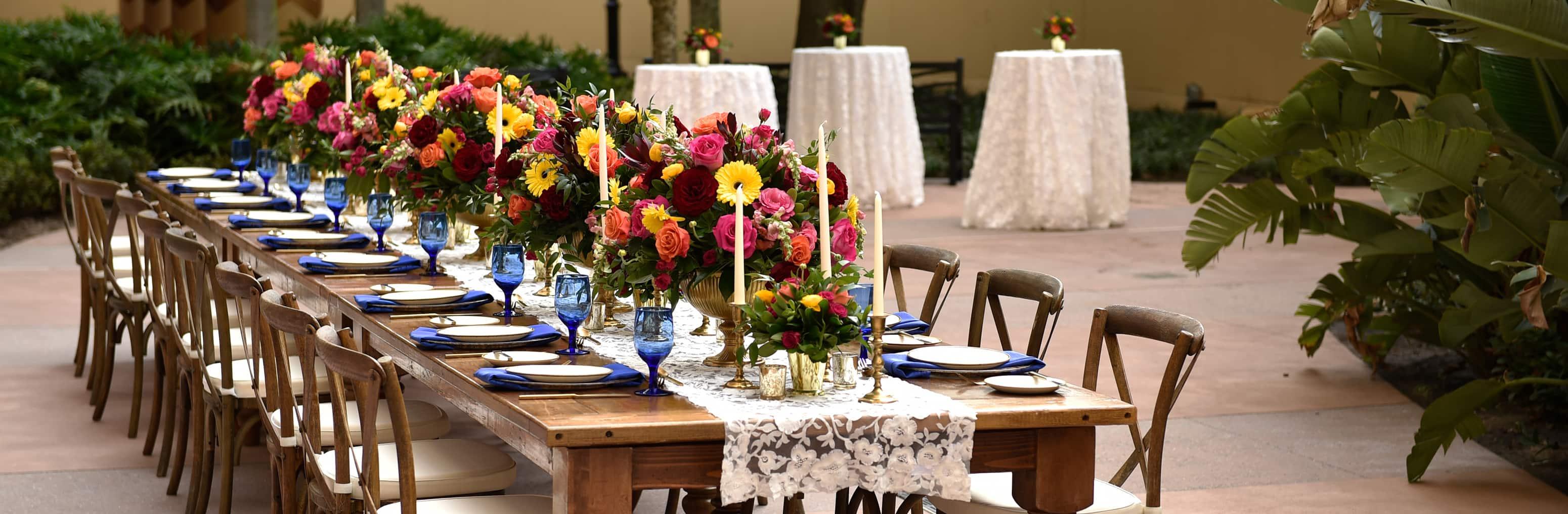 A long table with many place settings on a courtyard with 3 table tops in the background
