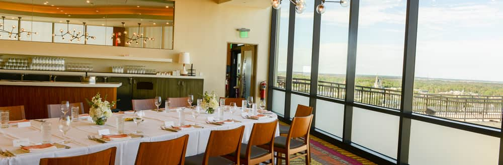 A long table set up near a bar and tall windows showing views of Cinderella Castle