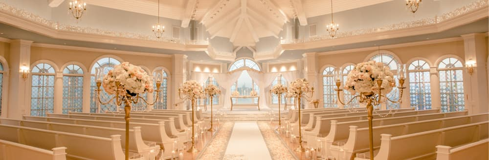 Sunlight shines through the arched stained glass windows of a wedding chapel with chandeliers and a high beam ceiling