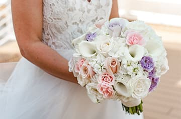 A bride holds a bouquet of roses and other flowers