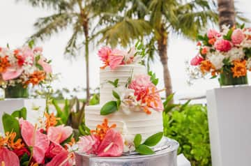 A wedding cake decorated with tropical flowers on a table near flowing palm trees