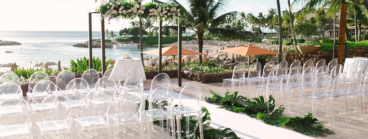 An outside patio arranged for a wedding ceremony overlooking a beach