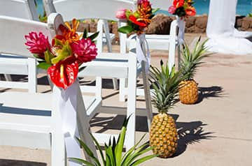 White folding chairs adorned with tropical flowers