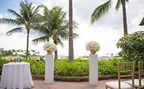 A table with candles and 2 flower stands grace a patio overlooking the ocean