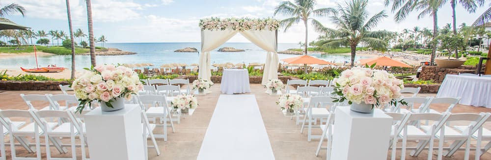 Two pillars holding rose bouquets line an aisle leading towards an altar outside