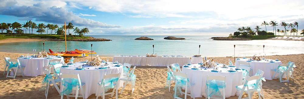 Several tables arranged on a beach with a view of the ocean