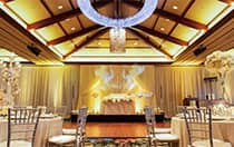 An elaborate light fixture hanging in the center of large room with many round tables and chairs